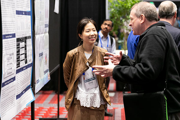 A poster presenter and attendee discuss her research.